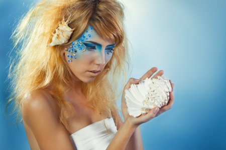 Beautiful girl with sea shell in hand, on a blue background Stock Photo