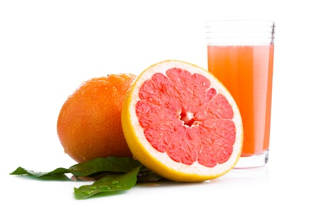 Grapefruit with leaves and fruit juice in a glass on a white background Stock Photo