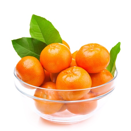Tangerines in a glass bowl with green leaves. On a white background Stock Photo