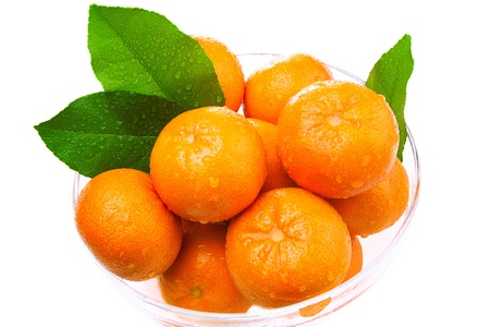 Wet tangerines in a glass bowl with green leaves. On a white background Stock Photo - 18370737