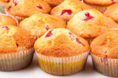 Lots of tasty cupcakes with cranberries in paper molds Stock Photo