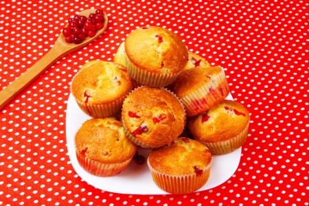 Cranberry muffins on a white plate. Red tablecloth with white polka dots