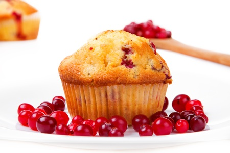 Cake on a plate with cranberries. Wooden spoon with cranberries in the background