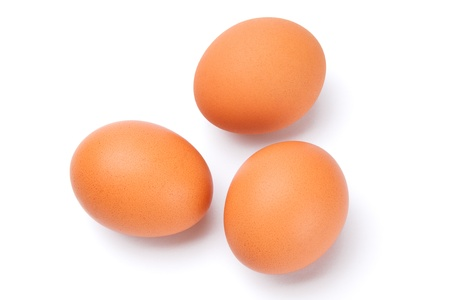 three fresh brown eggs isolated on white