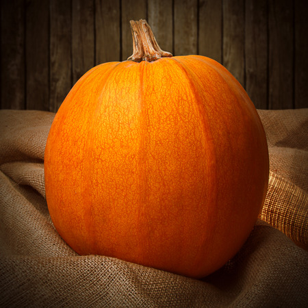 Orange pumpkin on the sackcloth with wooden background