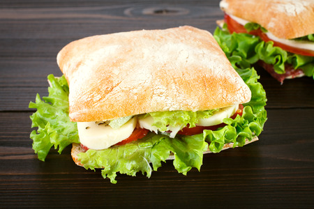 italian sausage: Sandwich with fresh mozzarella, tomatoes and lettuce on a wooden background.