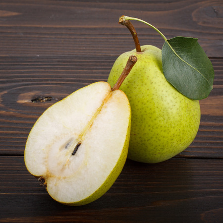 One and a half ripe pears on a wooden background Stock Photo