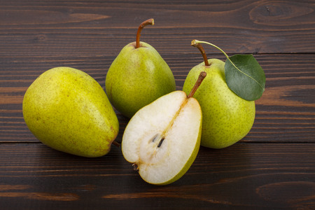 Three and half ripe pears on a wooden background Stock Photo