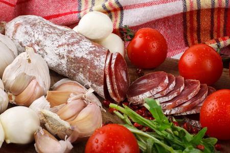 Salami with cherry tomatoes, arugula and garlic on a cutting board. Close-up Stock Photo