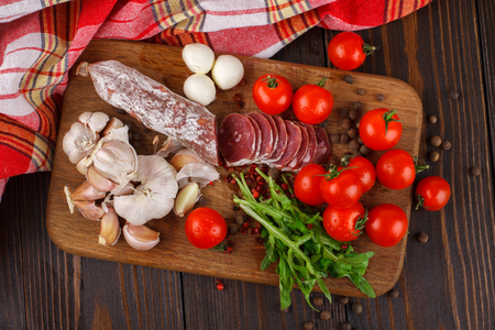 Salami with cherry tomatoes, arugula and garlic on a cutting board Stock Photo