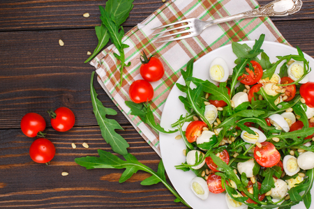 Salad with arugula, cherry tomatoes, mozzarella, quail eggs and pine nuts on a wooden background
