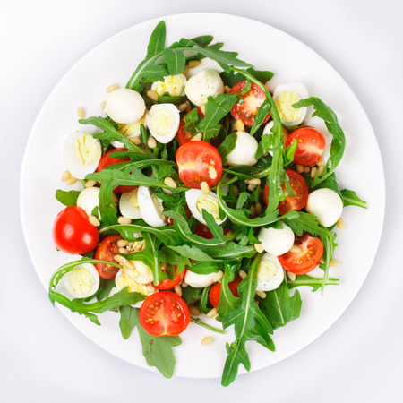 Salad with arugula, cherry tomatoes, mozzarella, quail eggs and pine nuts on a white background Stock Photo