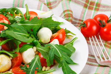 Salad with arugula, cherry tomatoes, mozzarella, quail eggs and pine nuts on a fabric background