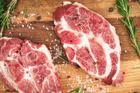 Porky steak with salt, pepper and rosemary on wood background. Top view.