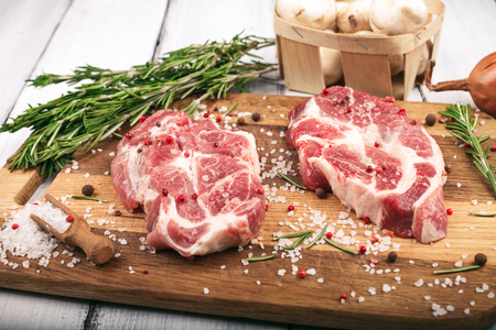 Porky steak with salt, pepper and rosemary on wood background.
