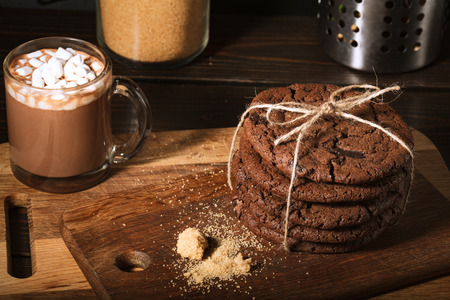 Ream of chocolate cookies on wooden board. Black backdround. Kitchen tools