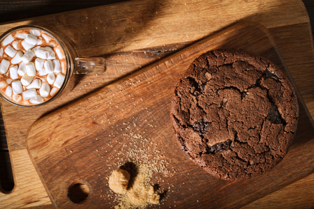 Ream of chocolate cookies on wooden board. Cup of cocoa with marshmallows Stock Photo