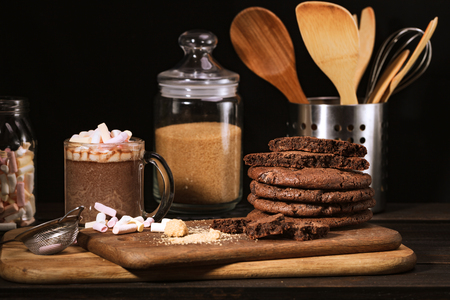 Ream of chocolate cookies on stone board. Black backdround. Kitchen tools