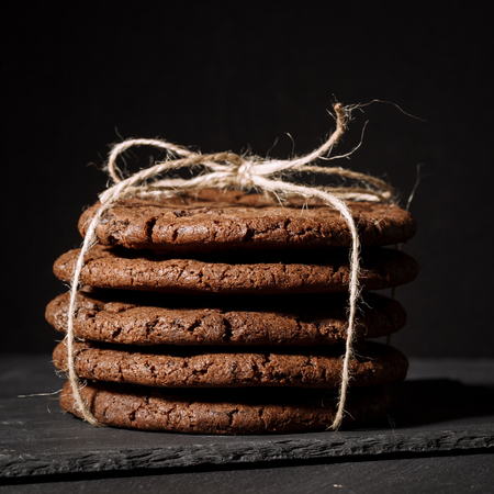 Ream of chocolate cookies on stone board. Black background.