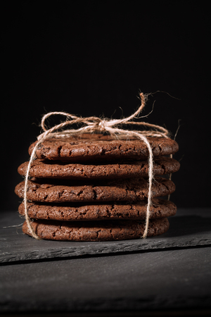 Ream of chocolate cookies on stone board. Black background. Stock Photo