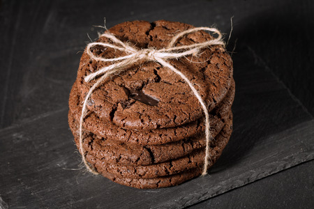Ream of chocolate cookies on stone board. Black backrround. View on top
