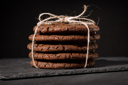 Ream of chocolate cookies on stone board. Black backrround.
