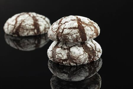Home made chocolate chip cookies with cracks. Covered with white powdered sugar. On a black background.