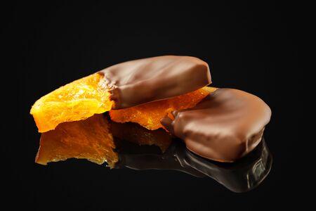 Delicious slices of orange in chocolate  on black background 版權商用圖片 - 127818353