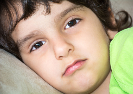 Close up of sad indisposed mirthless very young child boy with his thoughts drifting away.