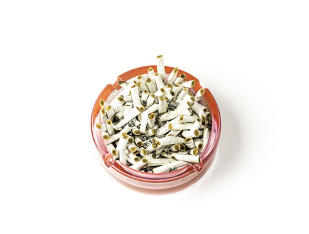 Close up of glass ashtray full of cigarette stubs isolated on white, top view. Copy space. Unhealthy lifestyle concept.
