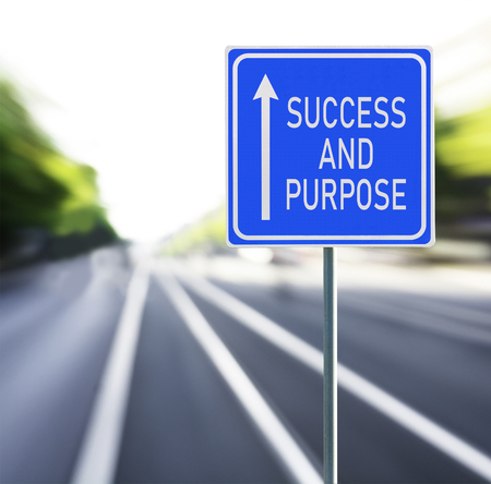 Success and purpose motivational phrase on blue road sign with arrow and blurred speedy background copy space