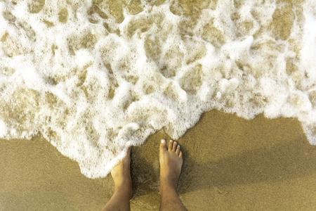 Vue de dessus sur les pieds sur l'espace de copie de la plage de sable - Fond de texture de la mer écumante océan tout en se tenant pieds nus sur la plage de sable fin - Point de vue sur les jambes avec fond d'été de l'océan en mousse de mer