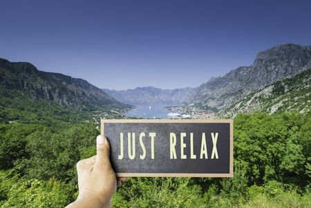 Just sit back relax and enjoy life sign on board mock up copy space overwrite view on summer bay sea ocean ships vacation between mountains bay no worries composite image background backdrop unique