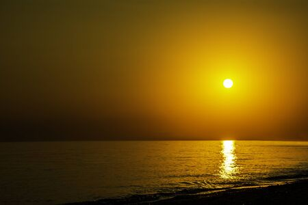 Horizontal sunset coastline calm sea with golden sun