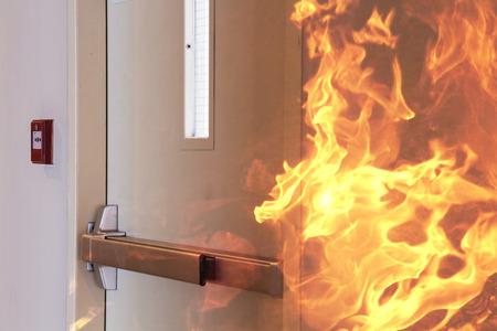 evacuacion: Fuego ardiente en frente de la puerta cerrada.