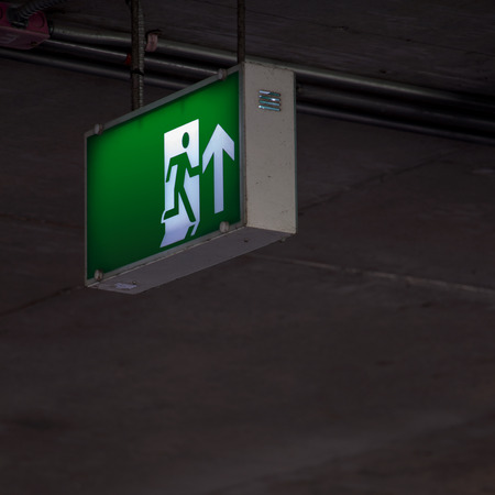 emergency exit: Emergency exit sign under the ceiling indoor at dark area. Stock Photo
