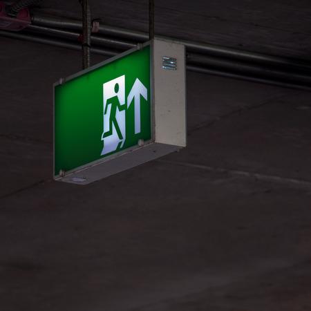 emergencia: señalización de emergencia bajo el techo de interior en el área oscura. Foto de archivo