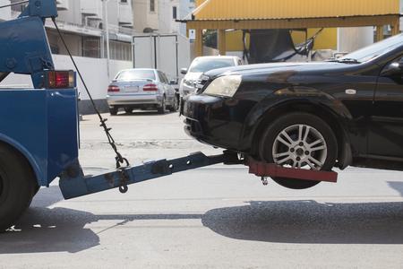 Black ar crash damage delivers to garage by blue truck.