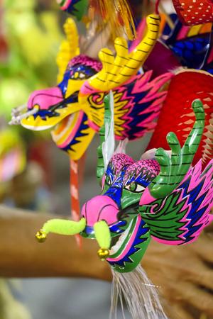 Dragon puppet paper mache handmade toy. Street photo china town Thailand.