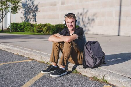Happy teenager sitting on the ground with his backpack while listening to some music.