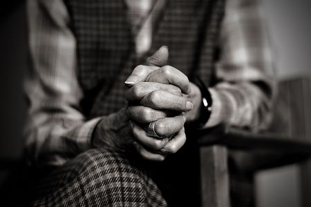 An old widow is praying while mourning her late husband Stock Photo