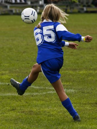 soccer girl giving the football a good kick Stock Photo