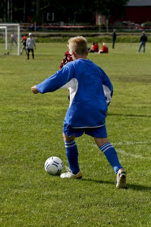 sportsmanship: kid dribbling with the ball at a soccer game