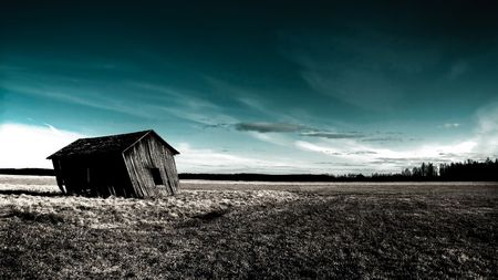 deserted haunted house on a empty field