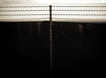 prison fence: dark old prison fence with barbed wire