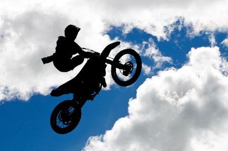 supercross: motocross rider making a high jump against a blue sky