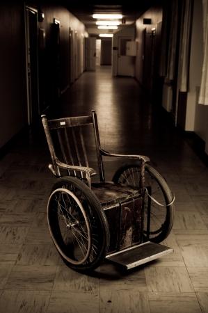 terapia psicologica: antigua silla de ruedas en un permanente vac�o corredor Foto de archivo