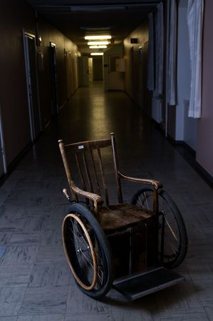 institution: old wheelchair standing in a empty corridor