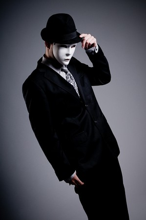 young man wearing a suit and a white mask