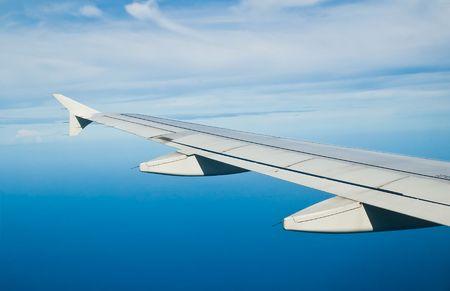 descending: an airplane descending over a blue ocean Stock Photo
